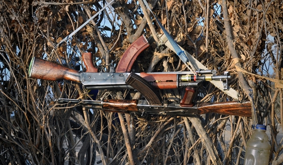 Two rifles belonging to Nyangatom men hang on a brush fence. (Photo by Luke Glowacki)